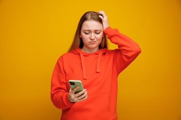 Betrokken jonge blonde vrouw die hand op hoofd houdt en mobiele telefoon bekijkt
