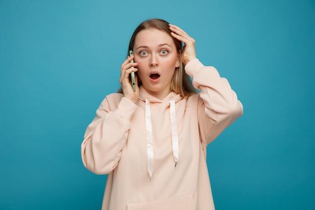Betrokken jonge blonde vrouw die op telefoon spreekt die hand op hoofd houdt