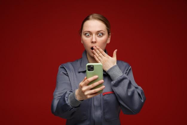 Betrokken jonge blonde vrouwelijke ingenieur die eenvormig bedrijf draagt en naar mobiele telefoon kijkt die hand op mond houdt