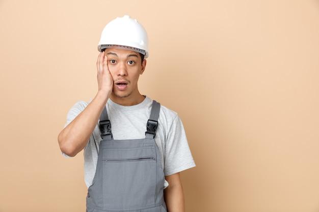 Betrokken jonge bouwvakker die veiligheidshelm draagt en eenvormig hand op gezicht houdt