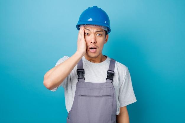 Betrokken jonge bouwvakker die veiligheidshelm draagt en eenvormig hand op hoofd houdt