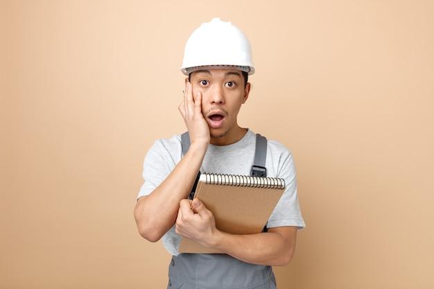 Betrokken jonge bouwvakker die veiligheidshelm en eenvormig holdingskladblok en potlood draagt die hand op gezicht houdt