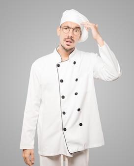 Betrokken jonge chef-kok die een gebaar van verwarring doet