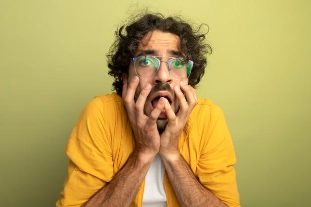 Betrokken jonge knappe blanke man die een bril draagt die handen op het gezicht houdt dat op olijfgroene muur met exemplaarruimte wordt geïsoleerd