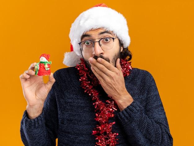 Betrokken jonge knappe kerel die kerstmuts met slinger op de nek draagt met speelgoed bedekte mond met hand geïsoleerd op oranje muur