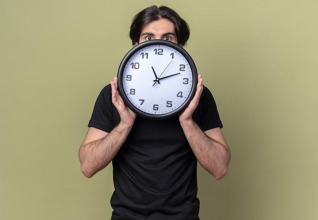 Betrokken jonge knappe kerel die zwart t-shirt draagt bedekt gezicht met muurklok die op olijfgroene muur wordt geïsoleerd