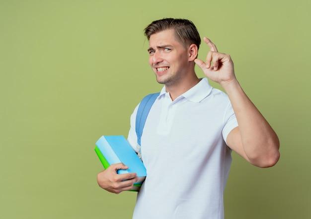 Betrokken jonge knappe mannelijke student die achterzak draagt die boeken en punten houdt omhoog geïsoleerd op olijfgroene achtergrond
