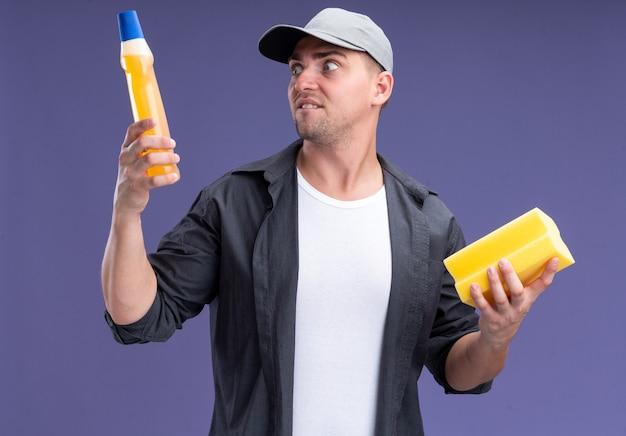 Betrokken jonge knappe schoonmaakster die t-shirt en pet draagt ?? die spons houdt en naar schoonmaakmiddel kijkt in zijn hand geïsoleerd op paarse muur