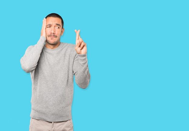 Betrokken jonge man doet een gebaar van gekruiste vingers