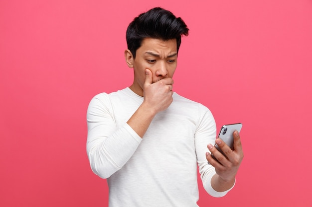 Betrokken jonge man houden en kijken naar mobiele telefoon hand op mond houden