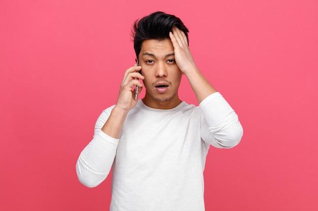 Betrokken jonge man praten over de telefoon hand op het hoofd houden Gratis Foto