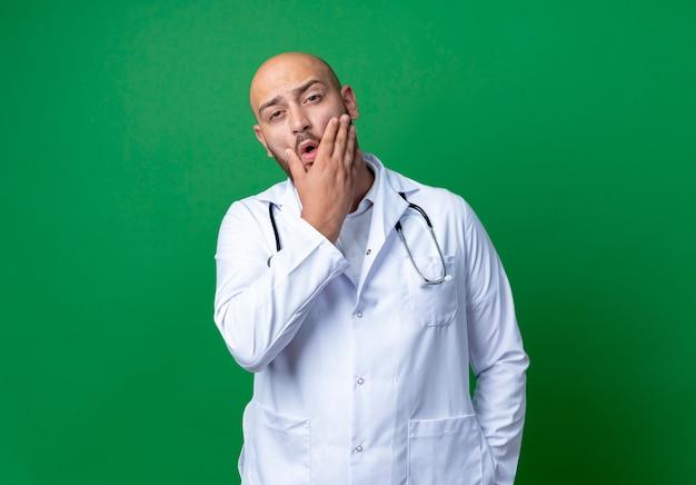 Betrokken jonge mannelijke arts die medische mantel en stethoscoop draagt die hand op wang zet die op groene achtergrond wordt geïsoleerd