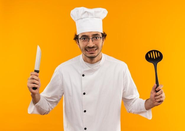 Betrokken jonge mannelijke kok die eenvormige chef-kok en glazen spatel en mes dragen