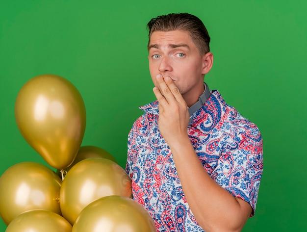 Betrokken jonge partijkerel die kleurrijk overhemd draagt dat zich naast ballons bevindt die hand op mond zetten die op groen wordt geïsoleerd