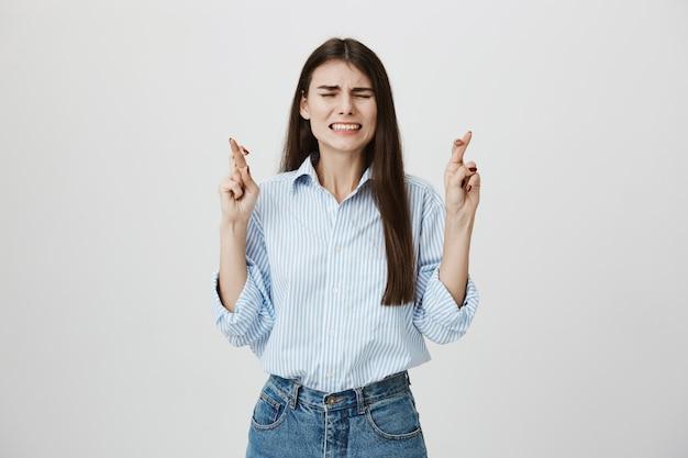 Betrokken jonge vrouw kruist vingers tijdens het smeken, klemt haar tanden op elkaar en sluit de ogen