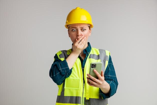 Betrokken jonge vrouwelijke bouwvakker die veiligheidshelm en veiligheidsvest draagt ?? die en mobiele telefoon bekijkt die hand op mond houdt