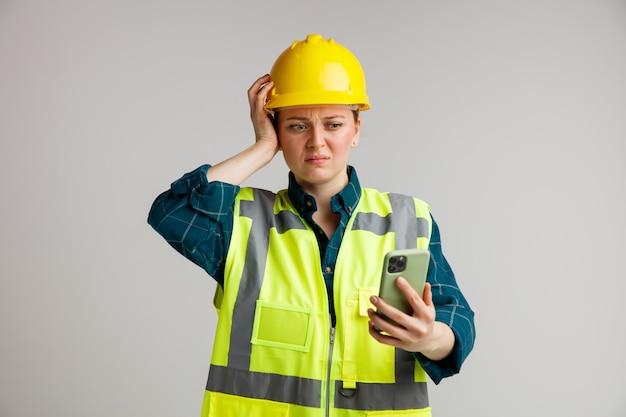 Betrokken jonge vrouwelijke bouwvakker die veiligheidshelm en veiligheidsvest draagt die hand op hoofd houden en mobiele telefoon bekijken