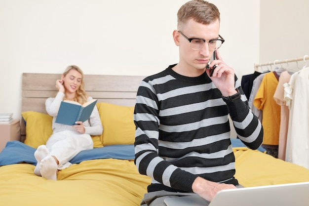 Betrokken jonge zakenman praten over de telefoon en het controleren van e-mails op laptop wanneer zijn vriendin roman in backgrouns leest