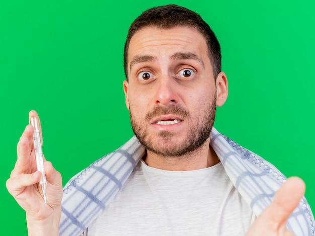 Betrokken jonge zieke man met thermometer met camera geïsoleerd op groene achtergrond