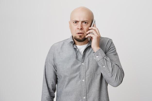 Betrokken kale man van middelbare leeftijd met een telefoongesprek