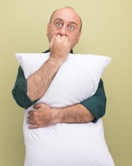Betrokken man van middelbare leeftijd met een groene t-shirt omhelsde kussen bijt nagels geïsoleerd op olijfgroene muur