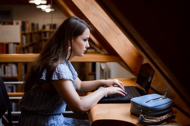 Betrokken studentenmeisje die met laptop het zitten in de bibliotheek werken en tekst typen