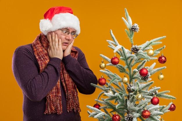 Betrokken volwassen man met bril en kerstmuts met sjaal om nek