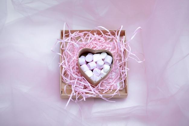 Betrokkenheid, getrouwde conceptfoto. roze marshmallow in geschenkdoos in vorm van hart op textiel achtergrond, veel marshmallows voor dit moment, zoete liefde. valentijnsdag. kopieer ruimte. close-up foto