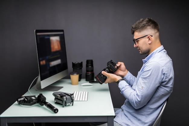 Betrouwbare fotograaf. vrolijke jonge man met digitale camera en lachend zittend op zijn werkplek