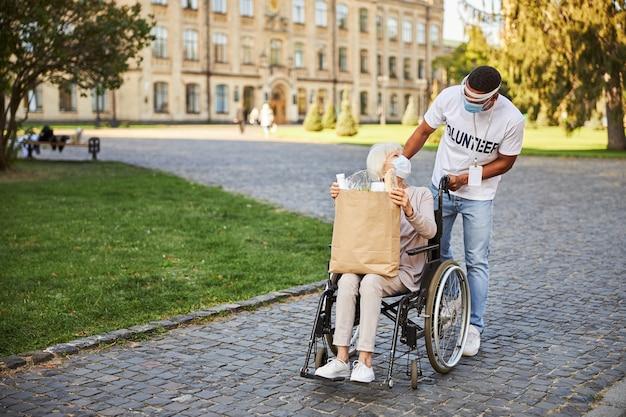 Betrouwbare vrijwilliger die een beschermend schild draagt terwijl hij na het winkelen naar de oudere dame in een rolstoel leunt met een papieren zak