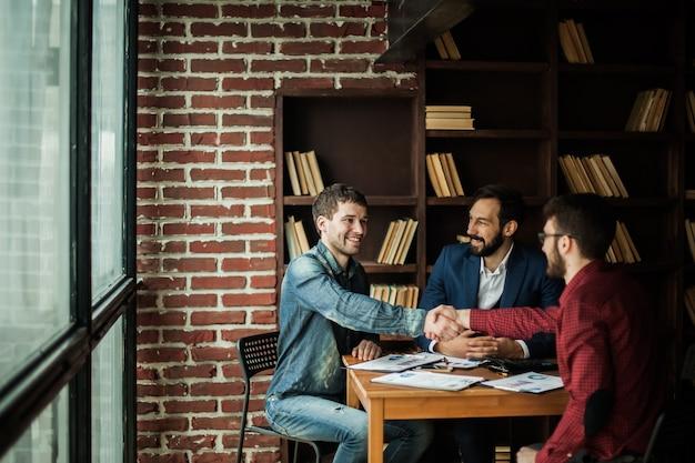 Betrouwbare zakenpartners schudden elkaar de hand na het bespreken van het contract voor de werkruimte op kantoor