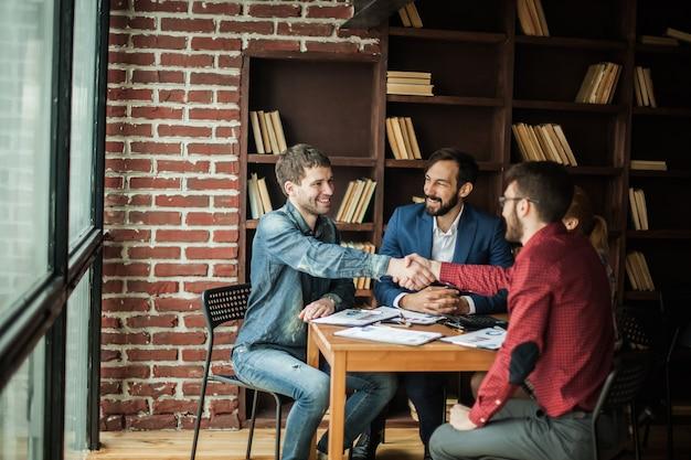 Betrouwbare zakenpartners schudden elkaar de hand na het bespreken van het contract