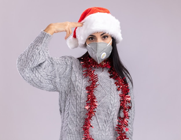 Beu jong kaukasisch meisje met kerstmuts en klatergoud slinger om nek met beschermend masker doen zelfmoordgebaar geïsoleerd op een witte muur met kopie ruimte
