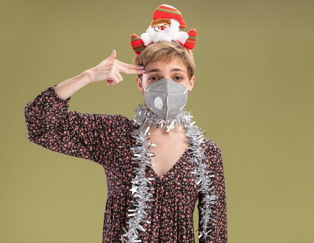 Beu jong mooi meisje dragen kerstman hoofdband en klatergoud slinger rond nek met beschermend masker kijken camera doen zelfmoord gebaar geïsoleerd op olijfgroene achtergrond