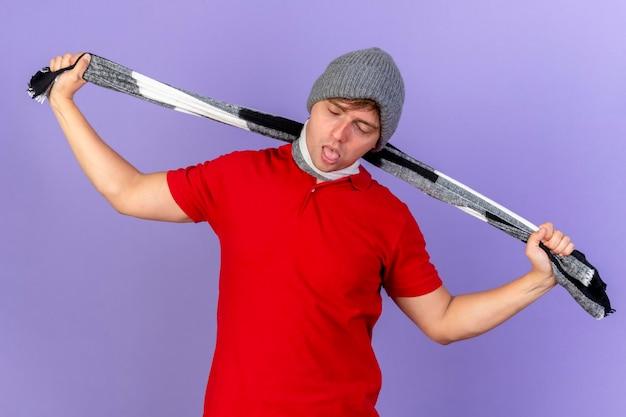 Beu jonge knappe blonde zieke man met winter muts en sjaal die zichzelf stikken met sjaal met gesloten ogen geïsoleerd op paarse muur