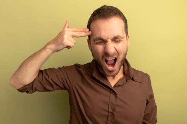 Beu jonge man doet zelfmoordgebaar met gesloten ogen geïsoleerd op olijfgroene muur