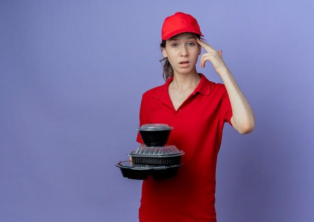 Beu jonge mooie levering meisje dragen rode uniform en pet houden voedsel containers doen zelfmoord gebaar geïsoleerd op paarse achtergrond met kopie ruimte