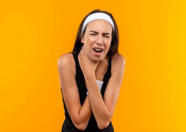 Beu jonge mooie sportieve meid met hoofdband en polsband die zichzelf probeert te stikken in de oranje muur