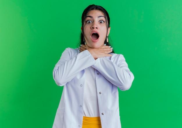 Beu jonge vrouwelijke arts die medische mantel draagt die op zoek stikt