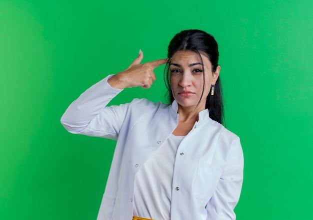 Beu jonge vrouwelijke arts die medische mantel draagt ?? die zelfmoordgebaar doet dat op groene muur met exemplaarruimte wordt geïsoleerd
