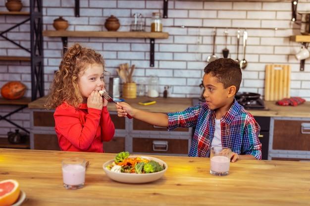 Beu. verlegen meisje met krullend haar dat positiviteit uitdrukt terwijl ze groenten eet