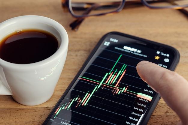 Beurshandel op draagbaar apparaatconcept. vinger aanraken van een grafiek op het slimme telefoonscherm op het bureau