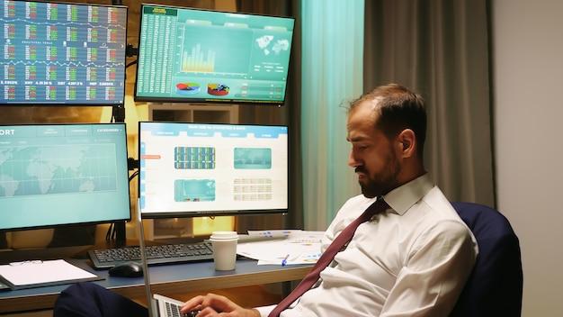 Beurshandelaar met pak en stropdas typen op laptop. economie crash.