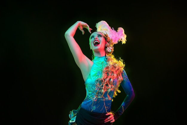 Bevallig. mooie jonge vrouw in carnaval, stijlvol maskeradekostuum met veren op zwarte achtergrond in neonlicht. copyspace voor advertentie. vakantie vieren, dansen, mode. feestelijke tijd, feest.
