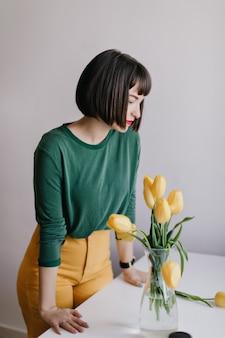Bevallige jonge vrouw die gele bloemen bekijkt. binnenportret van modieus donkerbruin meisje dat zich dichtbij vaas met tulpen bevindt.