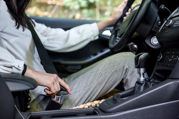 Beveiliging onderweg. vrouw stuurprogramma bevestiging veiligheidsgordel zit in auto