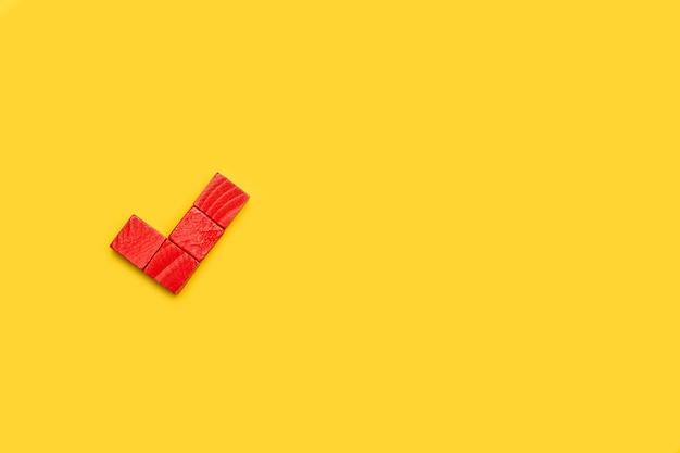 Bevestigend vinkje gemaakt met rode houten blokken op een gele achtergrond