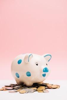 Bevlekte ceramische piggybank over muntstukken tegen roze achtergrond