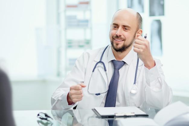 Bevoegde arts met een stethoscoop achter zijn bureau