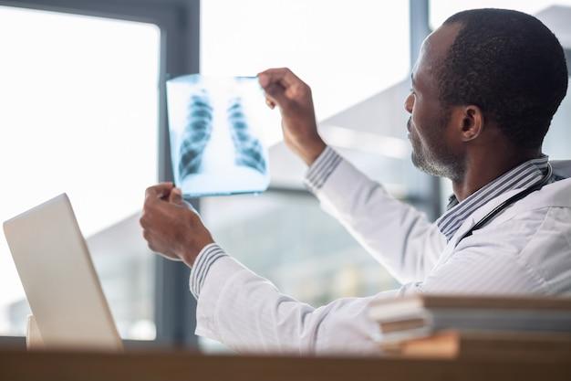 Bevoegde donkere man met röntgenfoto tijdens onderzoek